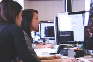Canva - Two Women Sitting in Front of Computer Monitor
