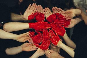 hands painted red to make the shape of a heart